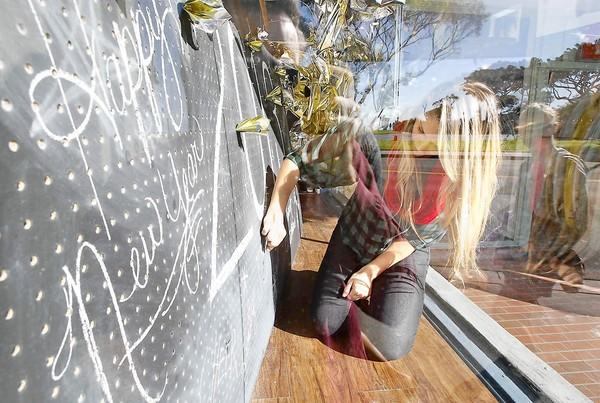 Sydney Hensler works on the New Year's Day-themed window display at Toes on the Nose surf shop.