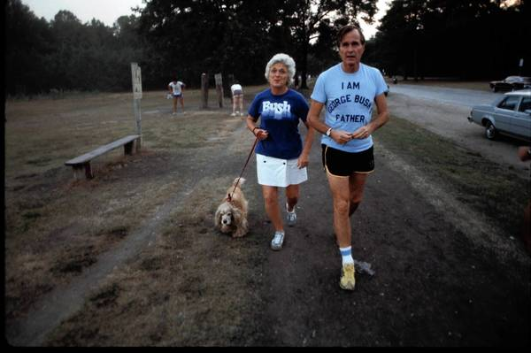 Republican presidential candidate George H.W. Bush wears a t-shirt referencing his son George W. Bush, as he walks with his wife Barbara and dog Fred in November 1978 in New Hampshire.
