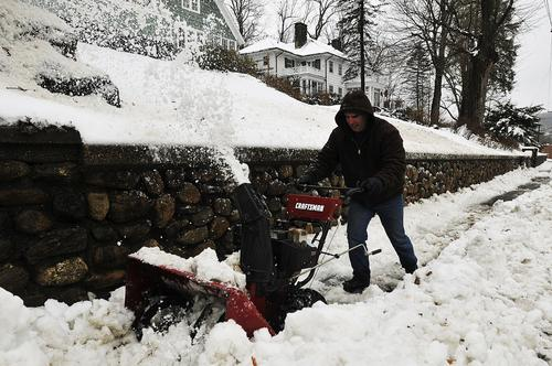 Jay Sullivan of Winsted tries to removed the snow from the sidewalk in front of his and his neighbors house on Hinsdale Ave Thursday during his lunch hour. The northern part of the state received the most snow before it turned to rain.