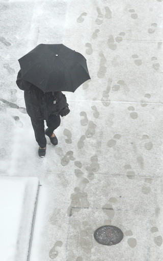 A wet mix of snow and rain had pedestrians using umbrellas  along the sidewalks in the 1800 block of Orleans St. on Wednesday.