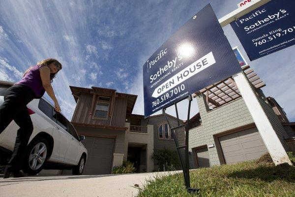 A woman arrives at a viewing for brokers of a home just put on the market in Leucadia, Calif.