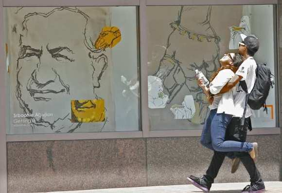 A couple walks by artwork by Srboohie Abajian in the storefront at 108. W. Broadway on Thursday, May 24, 2012.