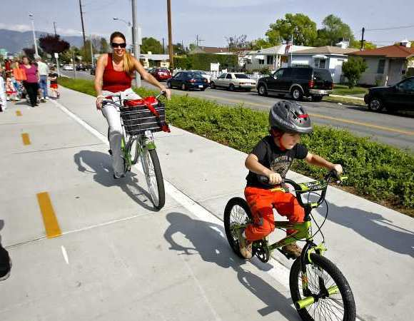 Residents use the Chandler Bikeway in Burbank, where the number of distressed homes on the market dropped in November.