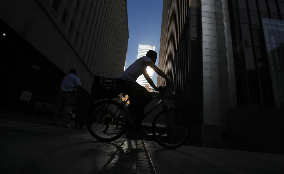 A bicyclist rides amid the shadows of tall buildings along Wilshire, in one of the stretches lined by dense development. (Luis Sinco / Los Angeles Times)