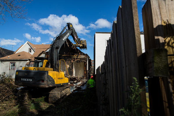 Crews demolish a house at 13 E. 113th St., which is the 200th building torn down under the mayor's initiative.