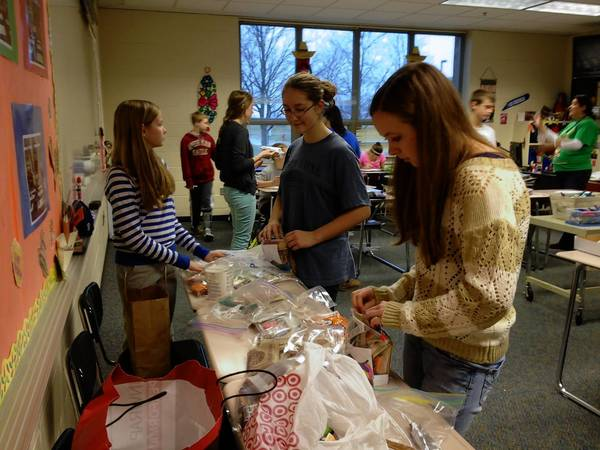 Geneva middle schoolers Emma Johlie, Monica Haughan and Tristan Williams, all 13, load bags to send to military men and women overseas.