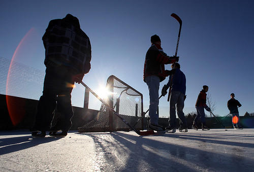 A group of Aberdeen teens warm up on the ice late Tuesday afternoon as they prepared for a pick-up game of hockey at Mother Joseph Manor Park. Bright sunshine and temperatures in the lower 20's made for a more Winter-like day compared to recent warmer days. photo by john davis taken 2/7/2012