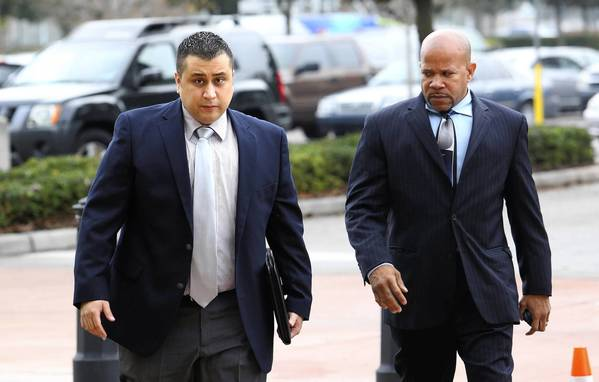 George Zimmerman is escorted by a private security guard as he arrives at the Seminole County courthouse for a hearing, December 11, 2012, in Sanford, Florida.
