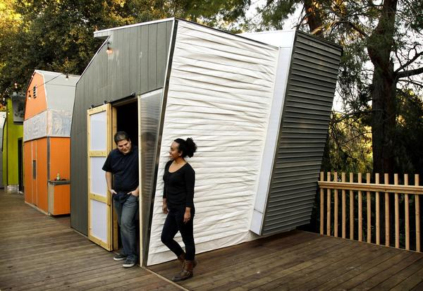 Jose Siquina, 27, and Leslee Rodas, 23, stand outside of their therapy-themed cabin, meant to be used as a space cabin for talk and physical therapy. They installed inexpensive pleated Tyvek and recycled vinyl baseboards from Home Depot as exterior siding.