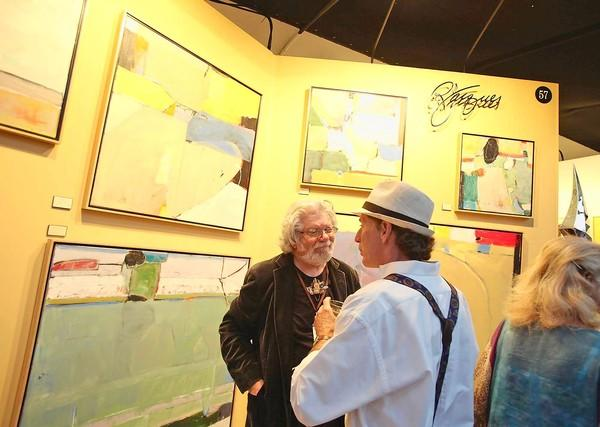 Acrylic artist Russell Jacques, left, speaks with a guest at his exhibit during Festival of Arts opening night party earlier this year. Organizers reported that with $9.4 million in gross revenue, they exceeded financial projections.