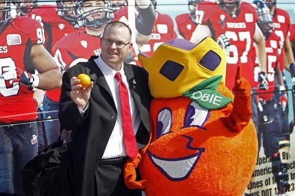 Interim Northern Illinois football coach Rod Carey poses with Obie, the Orange Bowl mascot, as the team arrives in Miami on Dec. 26.