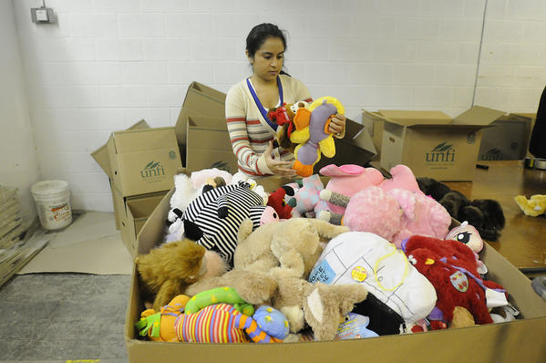 Zaynah Abid, a volunteer from Killingworth, sorts through donations which have been coming into Newtown by the thousands since the Newtown tragedy. The stuffed animals are sorted by size and Teddy Bears are one separate category, she said.