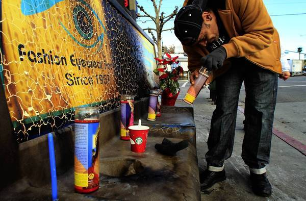 Phillip Furtado lights a candle to pay his respects to a homeless woman who was set on fire while sleeping on the bus bench.