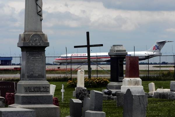 An American Airlines jet taxis adjacent to the cemetery in 2009, before those resting there were disinterred and relocated.