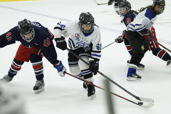 The CT Polar Bears' Andrea Noss works the puck against the PA Lady Patriots' Sarah Fothergill in the third period during the CT Polar Bears Girls Ice Hockey Tournament at the Trinity Community Sports Complex. The Polar Bears won, 3-1.