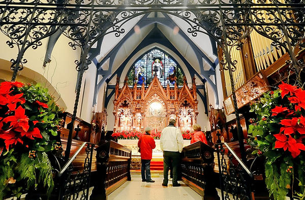 People stand in the nave to look at the altar and reredos at St John's Episcopal Church on South Prospect Street in Hagerstown during the Houses of Worship Holiday Tour.