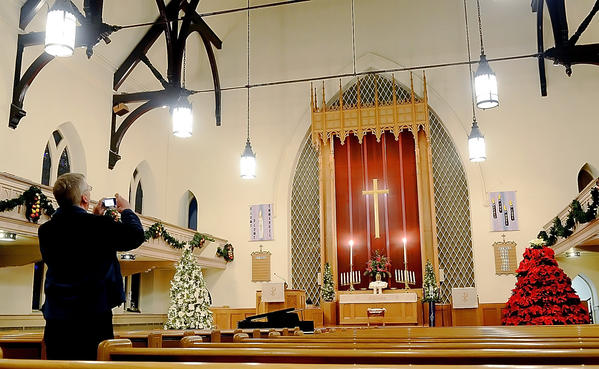 A visitor takes a photograph of the altar at John Wesley United Methodist Church on North Potomac Street in Hagerstown during the Houses of Worship Holiday Tour.