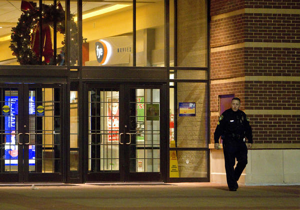 Police officers work the scene following a fight at Patrick Henry Mall on Thursday evening. Six people were detained and five people were charged in the incident, which forced the mall to close for the night.
