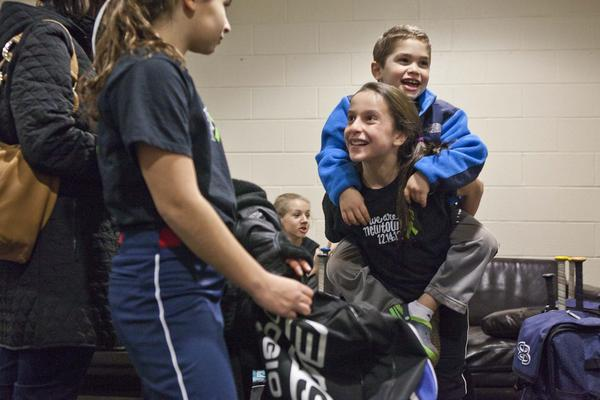 Olivia Mubarek, 12, smiles while holding Michael Berry, 6, on her back. Mubarek played an indoor softball game for Newtown against Monroe at Fast Pitch Nation in Bloomfield Thursday night. At left stands Amanda Berry, 12, another player on the Newtown team.