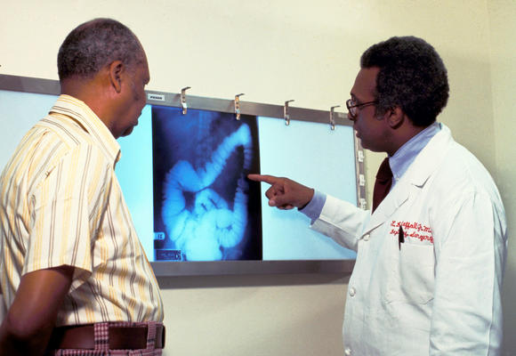 A doctor goes over a patient''s x-ray, screening for colon cancer.
