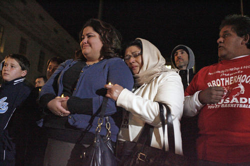 Robin Quintanilla, center, is comforted by her mother, Ana, during a vigil for Los Angeles County Sheriff's Department technician Victor McClinton, which took place at the Pasadena City Hall on Thursday, December 27, 2012.