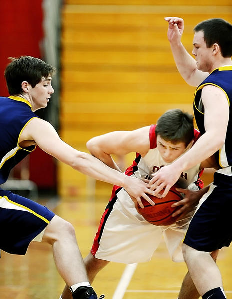 North Hagerstown's Max Ober, center, protects the ball against the defense of Loudoun County's Matt Adams, left, and Mike Anderson, right, during action at the Hubs Holiday Classic.