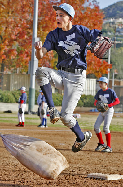 Will Smiley, 13, of La Crescenta, makes a throw and jumps over a stuffed sack that is imitating a base runner at the Annual Falcon Baseball Camp at Stengel Field in Glendale on Thursday, December 27, 2012.