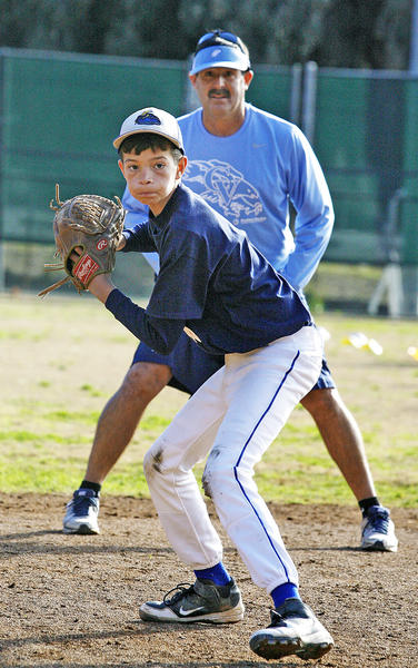 Chris Cancelosi, 11, of La Crescenta, with Crescenta Valley baseball coach Phil Torres watching, shuffles before making a throw during a drill at the Annual Falcon Baseball Camp at Stengel Field in Glendale on Thursday, December 27, 2012.