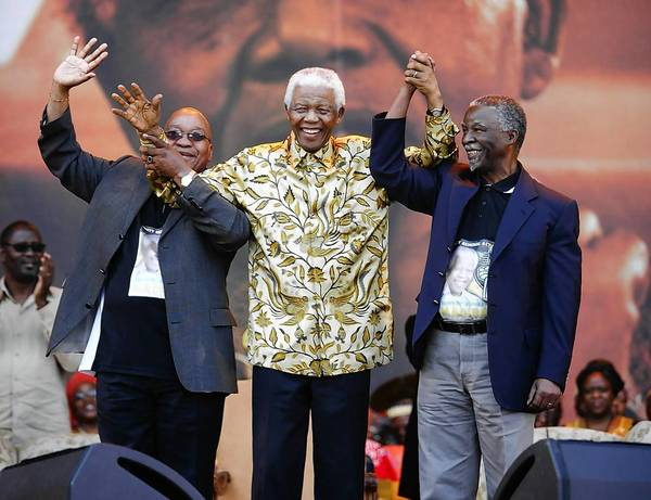Former South African President Nelson Mandela, President Thabo Mbeki, right, and African National Congress (ANC) President Jacob Zuma, left, arrive at the ANC 90th birthday celebration for Mandela in Tswane, South Africa.