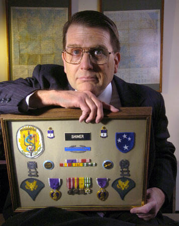 Vietnam veteran Eric R. Shimer shows his medals in his Bethlehem law office in April 2005. They include two Purple Hearts and the Combat Infantryman Badge. Behind him are maps of South Vietnam, where he fought.