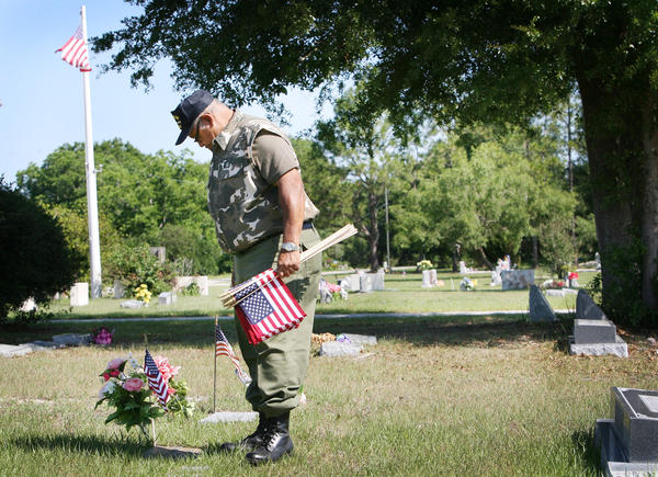 Robert Ragin, a Viet Nam vet places flags on veterans' graves on Monday, May 21, 2012 at Umatilla Cemetery. Veterans from American Legion Post 21 in Umatilla , placed flags on gravestones of those who served in the military in advance of Memorial Day. (Tom Benitez/Orlando Sentinel)