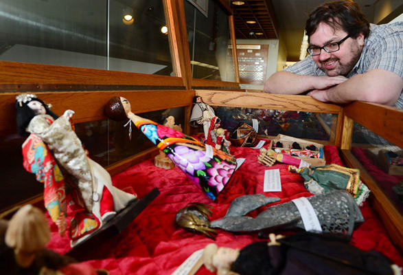 Benjamin Bertalan, Aquisitions Librarian at the Allentown Public Library, looks in the cases of dolls on display. Some of the 400 dolls from around the world from the collections of Harriet Backenstoe and Dorothy Knauss are on display at the Allentown Public Library.