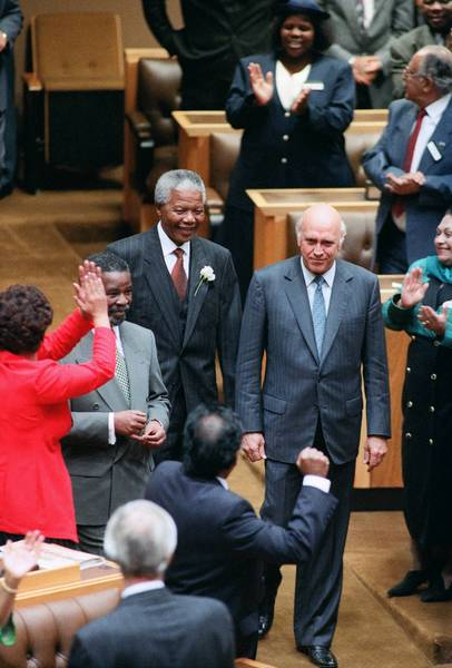 African National Congress leader and President-elect Nelson Mandela, center, and deputy presidents Thabo Mbeki, left, and Frederik W. de Klerk, right, receive cheers as they enter the inaugural sitting of South Africa's first all-race parliament in Cape Town, South Africa.