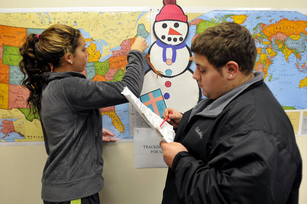 Michael Bardarelli reads off the state while Sabrina Fronte, 14, places a push-in in the maps of the country and world where a parcels for the Snowflakes Project came from at the Connecticut Parent Teacher Student Association which is collecting the snowflakes to create a Winter Wonderland for the kids of Sandy Hook Elementary School.