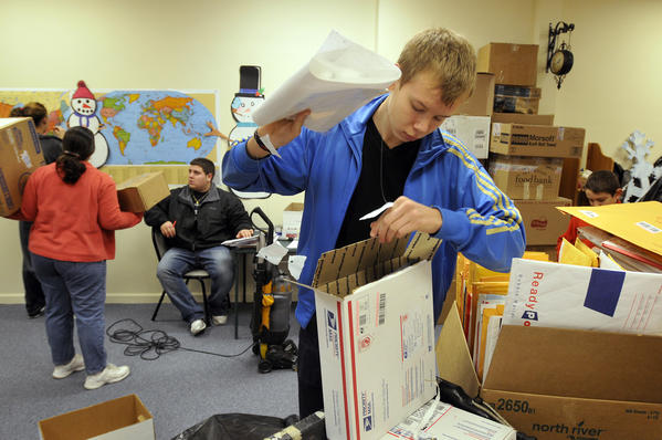 Hamden, CT 12/28/12 Anders Madsen, an exchange student from Denmark, sorts through one of the thousands of parcels delivered to the Connecticut Parent Teacher Student Association which is collecting snowflakes to create a Winter Wonderland for the kids of Sandy Hook Elementary School.