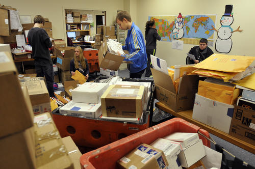 Hamden, CT 12/28/12 Thousands of parcels are pouring into the Connecticut Parent Teacher Student Association which is collecting snowflakes to create a Winter Wonderland for the kids of Sandy Hook Elementary School. Volunteers Andrew Rowe, 14 and his sister Leah, 15, exchange student Anders Madsen, 16, of Denmark, Sabrina Fronte, 14, and Michael Bardarelli, both of New Haven sort and catalog each of the packages then place a push-pin on the maps on the wall where they came from.