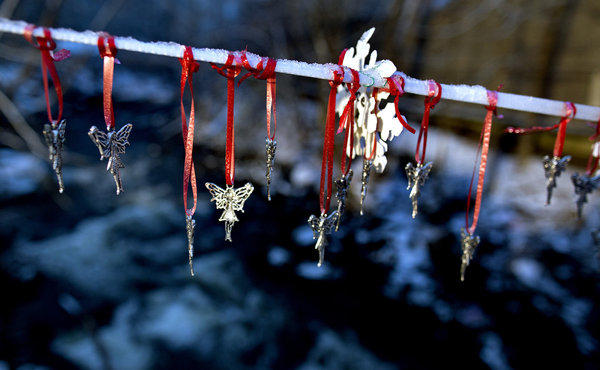 Angel pendants in memory of the schoolchildren killed at Sandy Hook Elementary hang from a snow-covered string in Newtown, Conn.