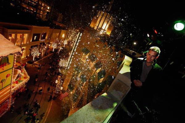 Adam Williams, owner of MagicSnow Systems, stands atop the Cheesecake Factory roof at the Grove during one of the L.A. shopping center's twice daily snow shows that blow snow down on shoppers with MagicSnow equipment.