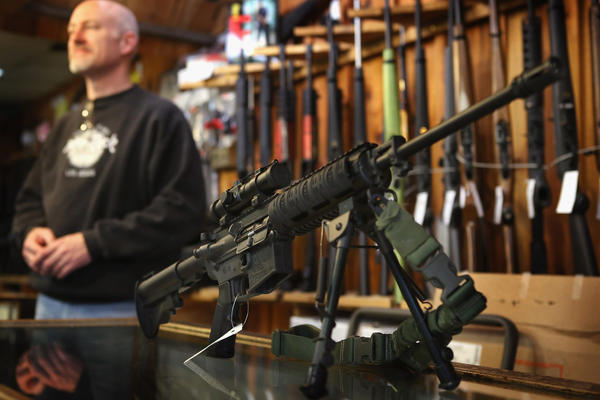 An AR-15 style rifle sits on the counter by Craig Marshall as he assists a customer at Freddie Bear Sports sporting goods store on Dec. 17 in Tinley Park, Ill.