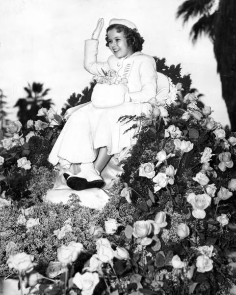 Grand Marshal Shirley Temple rides on a float covered with a bed of roses in 1939.