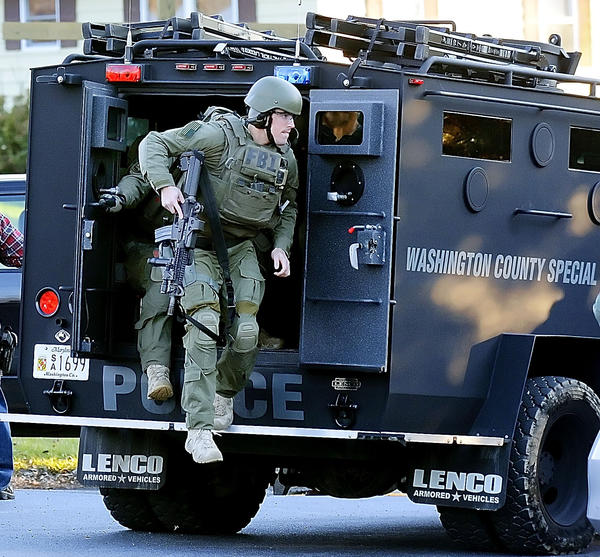 Agents from an FBI SWAT Team exit the Washington County Special Response Team's armored vehicle at the intersection of Burnside Bridge Road and Mills Road during a raid of a Sharpsburg-area man's property after receiving an anonymous tip that he had illegal firearms.