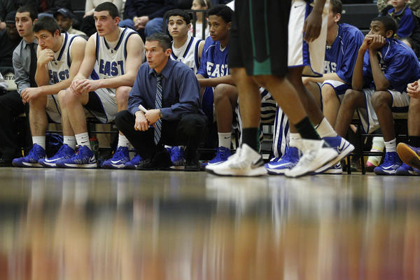 East Catholic coach Luke Reilly watches from the sideline as his team takes on Northwest Catholic during the second half at Wesleyan University's Silloway Gymnasium. East Catholic won, 67-56.