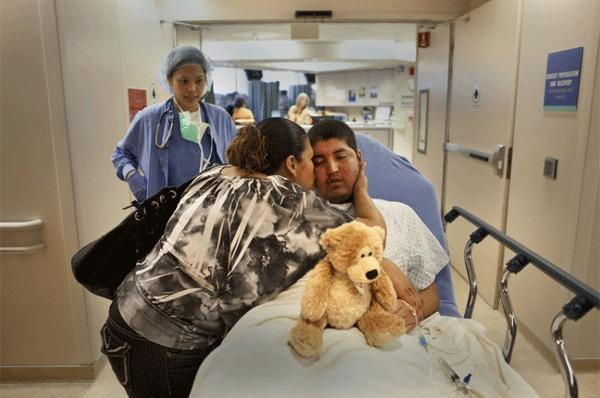 In the last moments before surgery, Valentina Gonzales kisses her son Jesus Garcia, 19, goodbye. Groggy from the anesthesia, Jesus is still clutching the teddy bear given to him by a nurse. The surgery lasted seven hours. Only a small amount of the tumor was removed and within a month after the surgery, the tumor had grown back.