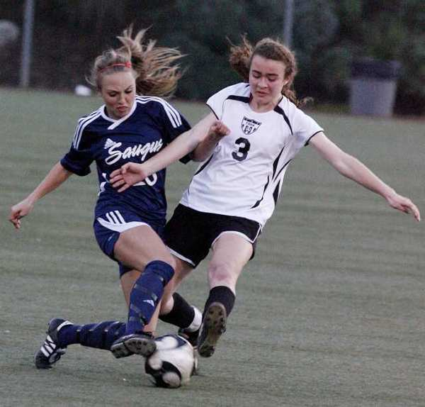 Saugus' Avery Schulhofer, left, drives into Flintridge Sacred Heart Academy's Lauren Savo as she dribbles.
