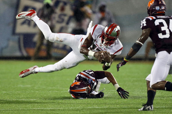 Rutgers Scarlet Knights wide receiver Brandon Coleman (17) leaps over Virginia Tech Hokies cornerback Kyle Fuller (17) in the rain during the second half of the Russell Athletic Bowl held at the Citrus Bowl. The Hokies defeated the Scarlet Knights 13-10 in overtime.