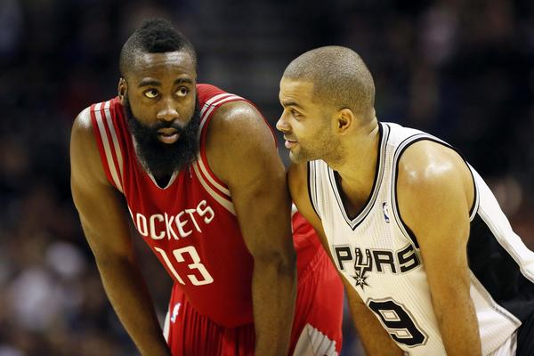 Houston Rockets guard James Harden (13) talks with San Antonio Spurs guard Tony Parker (9) during the second half at the AT&T Center.