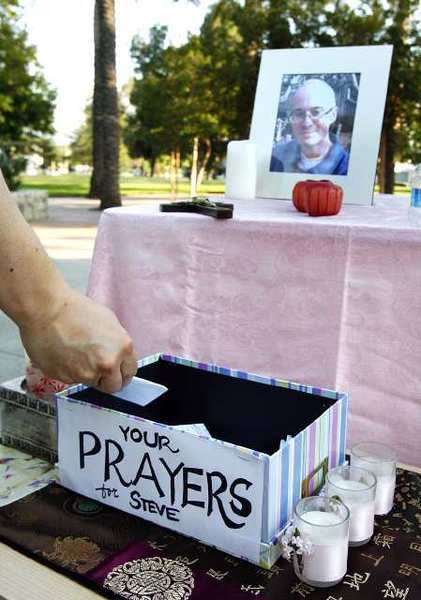 One of the guests drops a prayer he wrote into a prayer box at a prayer vigil for FBI agent Stephen Ivens at McCambridge Park in Burbank. Ivens' body was found by two hikers.