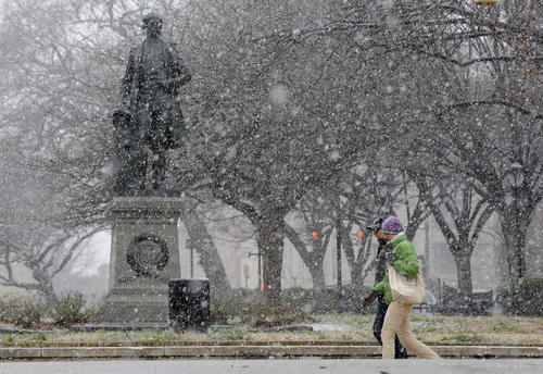 A light snow falls in Baltimore City this morning as pedestrians walk along St. Paul Street.