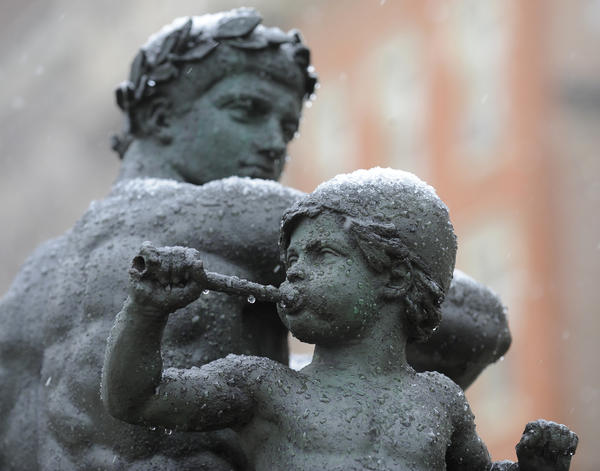 "A light snow falls in Baltimore City this morning starts to coat one of the statues names, ""War"" in Mount Vernon."