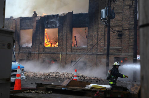 A Chicago firefighter works at the scene of a 4-11 alarm fire in a warehouse on the Southwest Side.